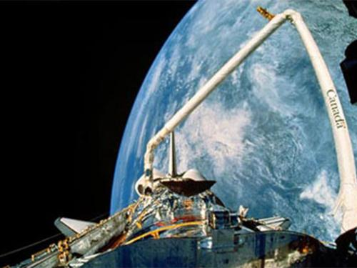 A view of the payload bay, Canadarm, and Earth