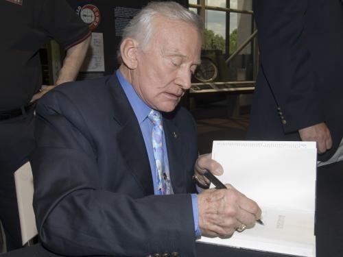 Buzz Aldrin signs book for a fan
