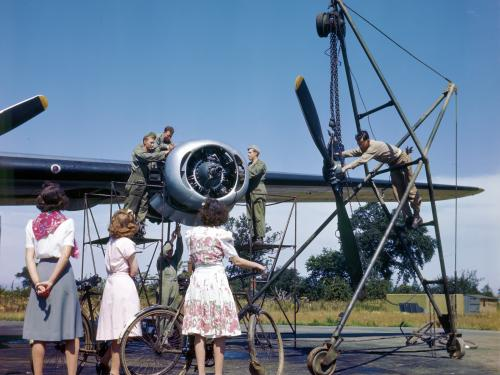 English women watch an Eighth Air Force maintenance crew work on a B-24 engine.