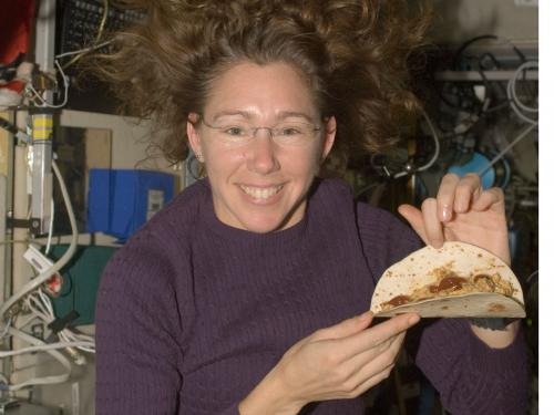 Astronaut Sandra Magnus poses for a photo with a tortilla sandwich which she prepared aboard the ISS.