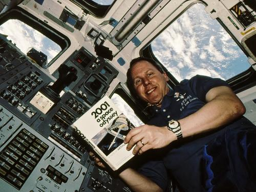 Astronaut Thomas D. Jones Holding Copy of 2001 A Space Odyssey During STS-98