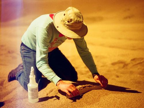 Geologist Jim Zimbelman bends over in the sand with a ruler.