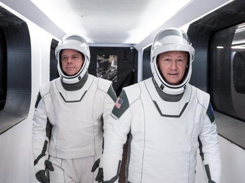 two astronauts in white spacesuits walk down hallway