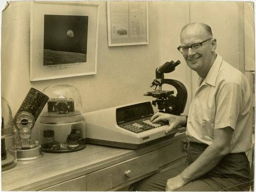 Man with glasses sits at desk.  On the desk are a microscope, telescope, camera and desktop calculator.
