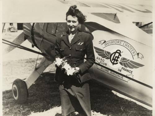 woman holding flowers in front of aircraft