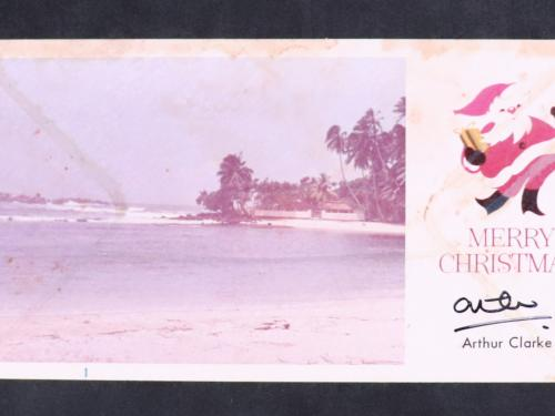 "Photo postcard. Left: beach with palm trees. Right graphic drawings of Santa Claus over preprinted text: ""Merry Christmas"" Handwritten signature. Preprinted text: ""Arthur Clarke"""