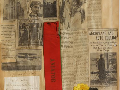 "Large Scrapbook page with newspaper clippings. Bottom right, white handwritten sheet; bottom middle; red rectangular ribbon ""Aviator""; bottom right: yellow flower attached ribbon ""Votes for women"""