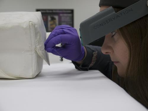 View of the repair being made to the tear in the Beta cloth medical container by Conservation intern Meghann Kozak