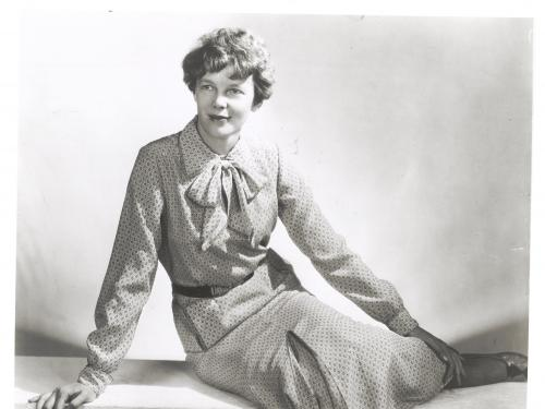Amelia Earhart sits with her legs to the side.