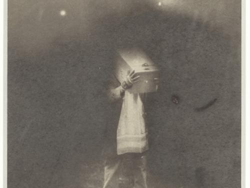 Black and white artistic photo of someone with a box over their head.