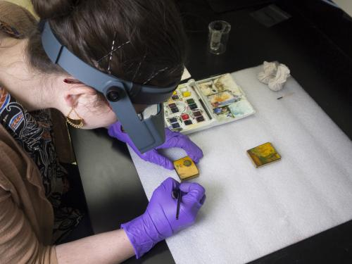A photo of Lauren Gottschlich, Engen Conservation Fellow, inpainting the losses on the lid with watercolor paints.