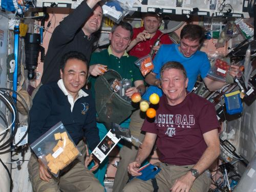Astronauts with floating fruit and bags of food