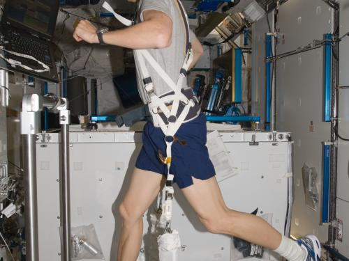 Expedition 34 Flight Engineer Tom Marshburn exercising on a treadmill aboard the ISS, 2012.