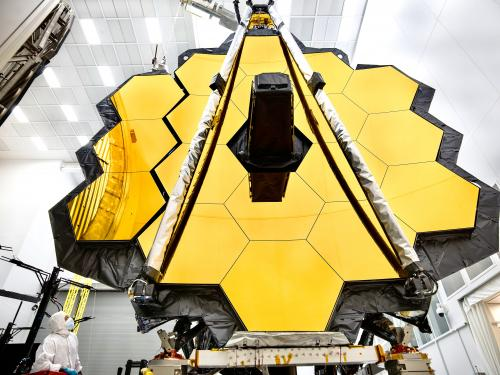 A close-up of a large space telescope, yellow honeycomb shape.