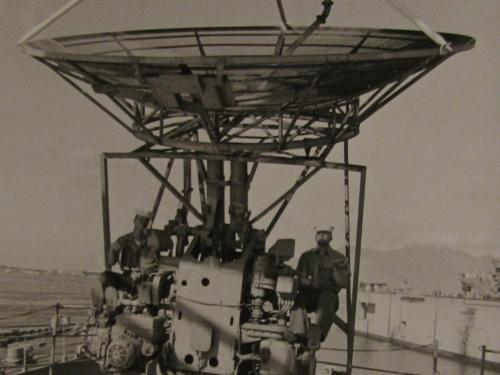 Black and white photo of two technicians installing antenna
