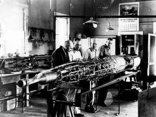 Robert Goddard works on a rocket with his team.