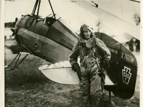 black and white photo of Amelia Earhart in front of an aircraft.