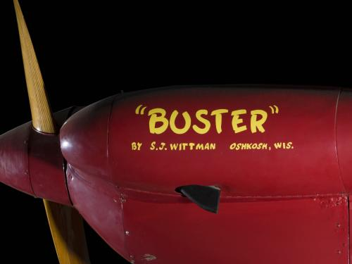 "Side of nose of red Wittman Special 20 ""Buster"" aircraft with """"Buster"""" and identification in yellow lettering"