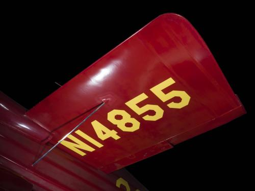 "Wing of red Wittman Special 20 ""Buster"" aircraft with ""NI4855"" in yellow lettering"