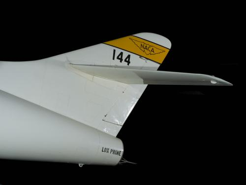"Tail of white Douglas D-558-2 aircraft with yellow stripe with ""NACA"" insignia and ""144"" written in black letters"