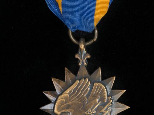 Bronze sunburst medal with eagle holding lightning bolts on blue silk ribbon with gold stripes