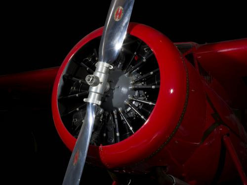 Front engine and silver single-blade propeller on red Amelia Earhart Lockheed Vega 5B aircraft