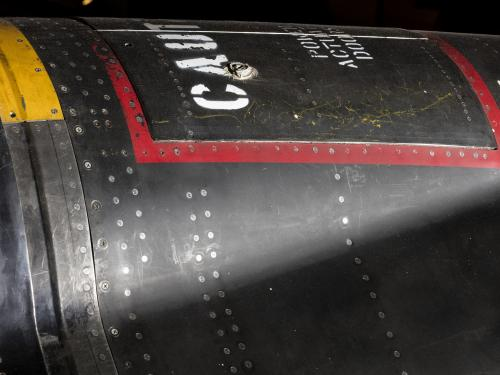 "Red square outline and ""Caution"" in white lettering on black titanium North American x-15 aircraft"