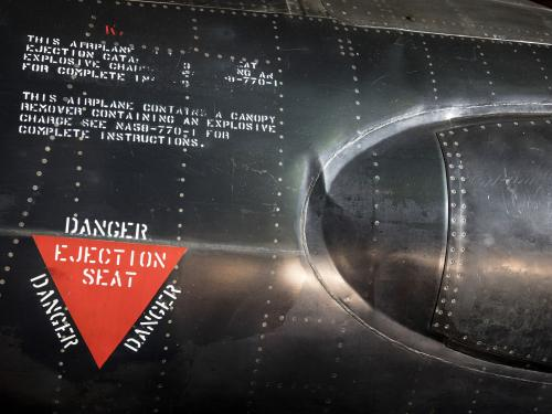 "Red triangle ""Danger Ejection Seat"" label on side of black titanium North American x-15 aircraft"