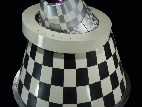 Rear view of an infrared sensor with black and white checkered cone with a ring mount.