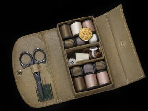 Rectangular box with thread spools, needles, buttons, and scissors