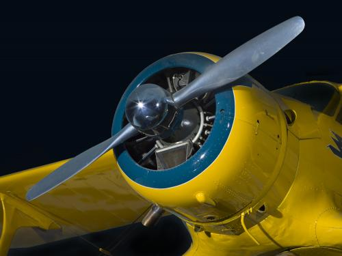 Closeup view of the two-blade propeller and engine from yellow Beechcraft C17L Staggerwing aircraft