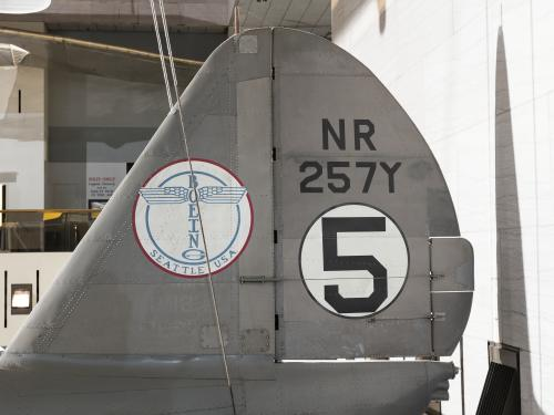 "Boeing logo and ""NR257Y"" with ""5"" in white circle on vertical stabilizer on gray Boeing 247-D aircraft"