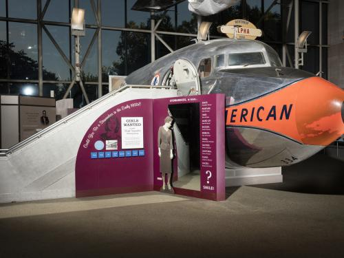Cutoff of Douglas DC-7 aircraft in museum with exhibit panels next to stairs into aircraft
