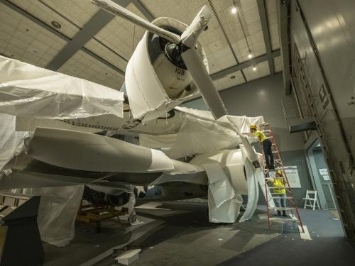 Contractors from Crozier Fine Arts work to protect the Hellcat aircraft.