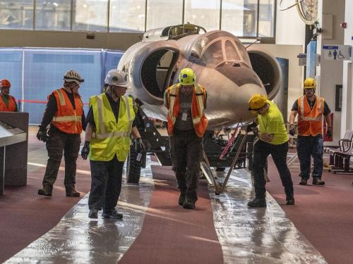 The forward fuselage of the Lockheed U-2 aircraft is moved by staff and contractors.