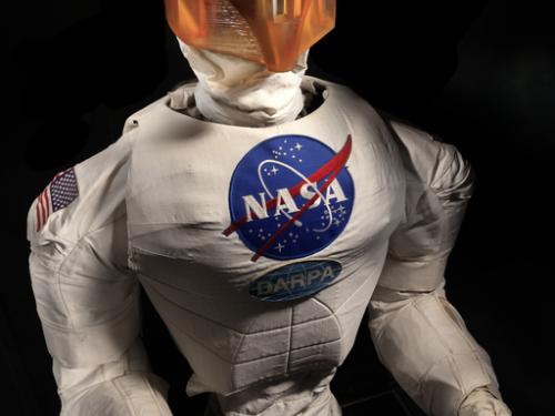 Frontal view of a body of a robot with arms, chest with a NASA logo, and an orange face cover.