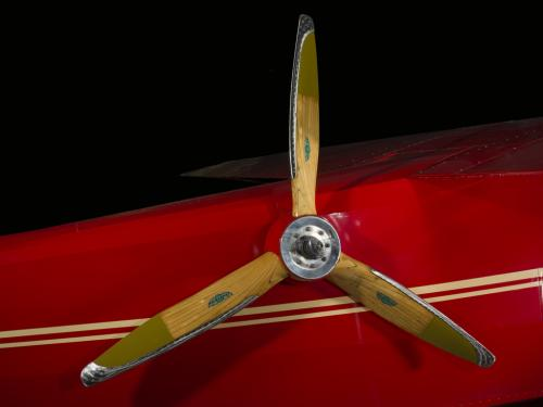 Close up image of a wood airplane propeller. The propeller is attached to a air plane.