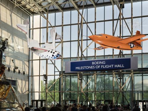 "Two airplanes hang from the ceiling in front of a glass wall that has the name ""Boeing Milestones of Flight Hall."""