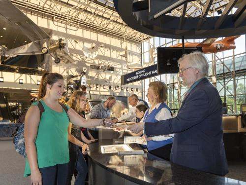 Visitors being helped by the Welcome Center in the Boeing Milestones of Flight Hall