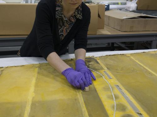 Conservator with purple gloves works over yellow rudder fabric.