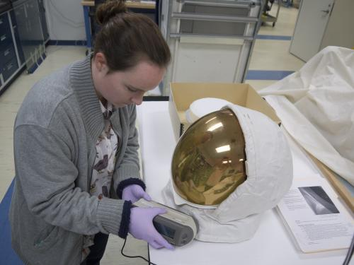 Conservator uses a device on a helmet.