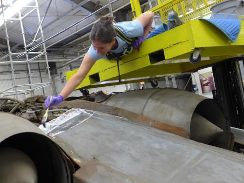 Conservator hovers above aircraft to clean it.