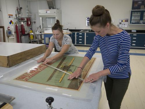 Two conservators working over an airplane print.