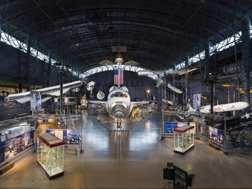 photo of the discovery space shuttle surrounded by artifacts within the Udvar-Hazy museum