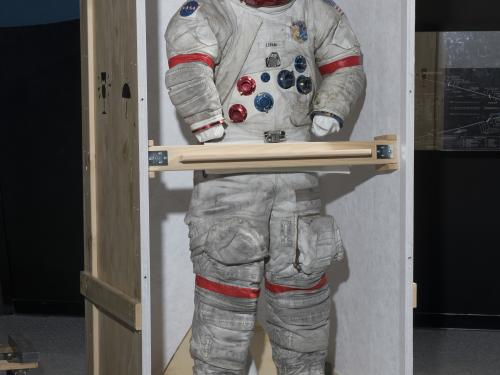 """Gene Cernan's Apollo 17 spacesuit being moved out of the exhibit case in the """"Apollo to Moon"""" gallery"""