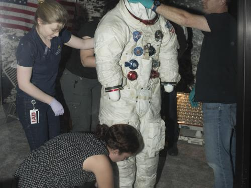 """Buzz Aldrin's Apollo 11 spacesuitbeing moved out of the exhibit case in the """"Apollo to Moon"""" gallery"""