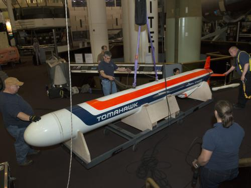 Staff encircle the missile as it's lowered to the ground.
