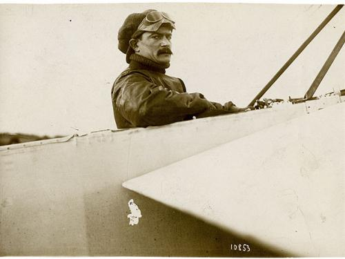 Black and white photo of Jules Vedrines seated in his monoplane. Vedrines stares directly at the photographer