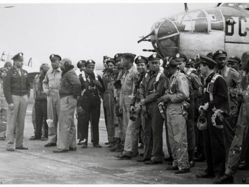 Group of African American airmen in front of aircraft