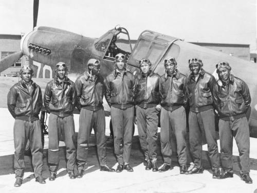 Eight men in jackets and aviation goggles in front of aircraft